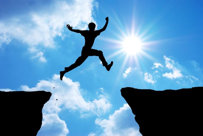 A man jumping across a cliff.