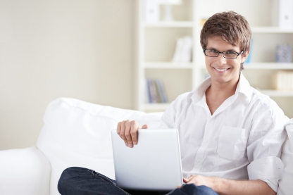 Smiling man with laptop at home